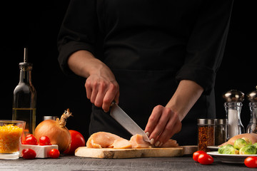 Chef slices chicken, for cooking, and salad. Against the background of vegetables, cooking and home recipe book
