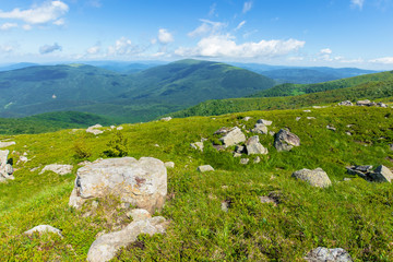 rocks on the alpine meadow. beautiful summer scenery of runa mountain. rural valley in the distance. sunny weather with fluffy clouds on the blue sky