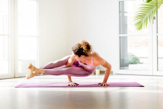 Young woman doing an arm balance yoga pose