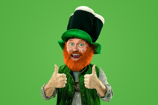 Nice, thumbs up. Excited leprechaun in green suit with red beard on green background. Funny portrait of man ready to party. Saint Patrick day, human emotions, celebration, traditional holidays.