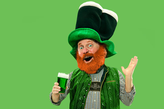 Pint of beer. Inviting. Excited leprechaun in green suit with red beard on green background. Funny portrait of man ready to party. Saint Patrick day, human emotions, celebration, traditional holidays.