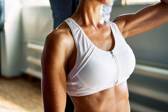 Close up photo of sporty woman in fitness bra with sweat water drop on skin