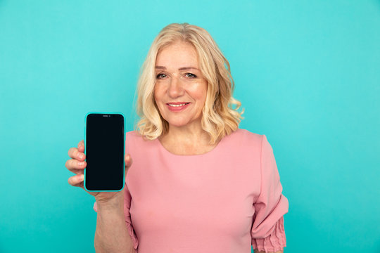 Happy mature woman pointing phone in the blue studio