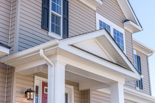 Portico leading to the entrance of vinyl horizontal lap siding covered building, with a roof structure over a walkway, supported by white rectangular columns on a new single family home in Maryland
