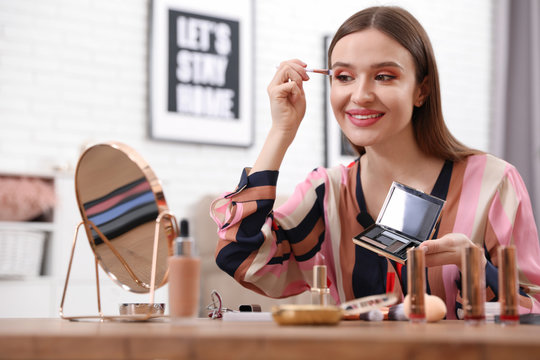 Young beauty blogger applying eyeshadow at home