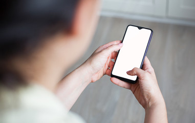 Mockup image of hand holding mobile phone with blank white screen