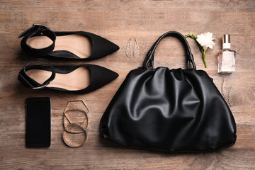 Flat lay composition with stylish shoes, woman's bag and smartphone on wooden background Wall mural