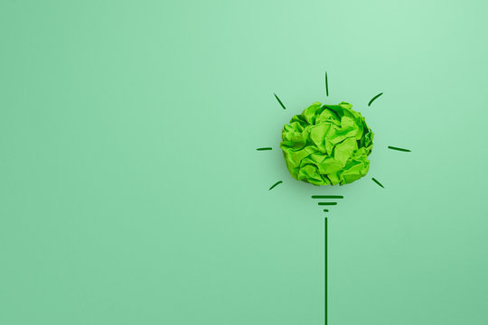Creative idea, Inspiration, New idea and Innovation with Corporate Social Responsibility (CSR) concept, Green crumpled paper light bulb on green background.