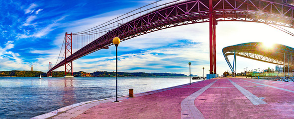 Lisbon landscape at sunset.Panoramic photograph of the 25 de Abril bridge in the city of Lisbon over the Tajo River Fotomurales