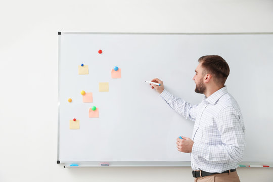 Portrait of young teacher writing on whiteboard in classroom