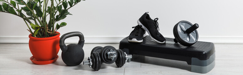 panoramic shot of sports stuff and sneakers at home with houseplant Wall mural