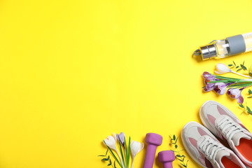 Flat lay composition with spring flowers and sports items on yellow background. Space for text