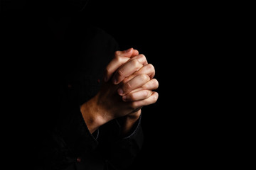 Image of praying hands on a black background
