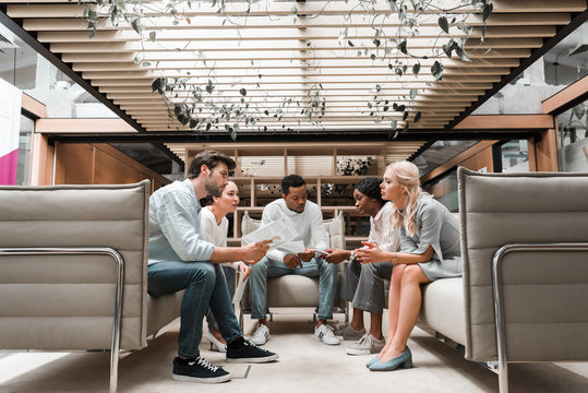 young multicultural businesspeople sitting in office lounge during meeting
