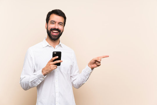Young man with beard holding a mobile pointing to the side to present a product