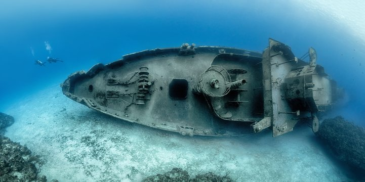 Divers examining the famous USS Kittiwake submarine wreck in the Grand Cayman Islands