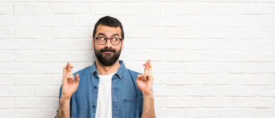 Handsome man with beard over white brick wall with fingers crossing and wishing the best