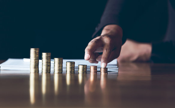 businessman use finger to climb level coins in a growing position, Investment concepts, financial growth and saving