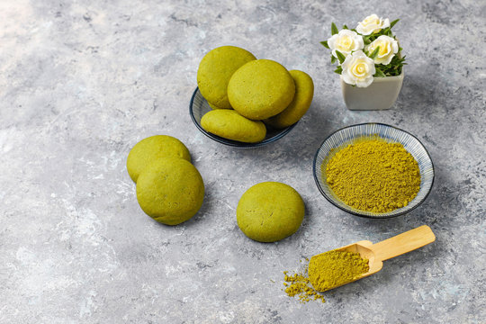 Homemade matcha green tea cookies with matcha powder on grey concrete background