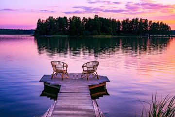Canvas Prints Light pink Two rattan chairs and glasses of red wine on a pier overlooking a lake at sunset in Finland