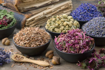 Keuken foto achterwand Lavendel Bowls and mortars of dry medicinal herbs: lavender, cornflower, coneflower, daisies. Healing herbs assortment and old books on wooden table. Herbal medicine.