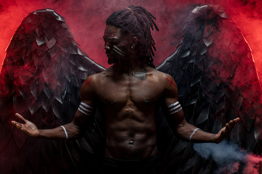 dark african angel with big black wings isolated, young serious muscular man wearing big wings on the back. strong angel come down from heaven. fantasy