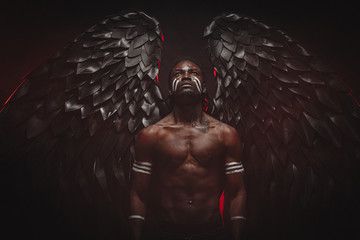 young strong black angel with cool wings, stand posing at camera. man fall from heaven, angel with muscular body gained freedom. fantasy concept, unusual creative photoshot