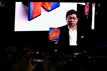 Richard You, CEO of Huawei Technologies Consumer Business Group holds a Huawei Mate Xs foldable smartphone as he talks to the audience on a big screen during Huawei stream product launch event in Barcelona