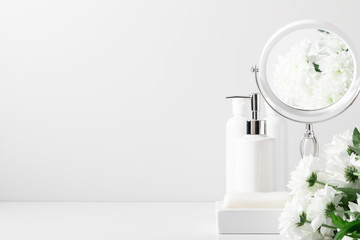 Soft light white bathroom decor, mirror, soap dispenser, white flowers, accessories on white shelf. Elegant decor bathroom interior.