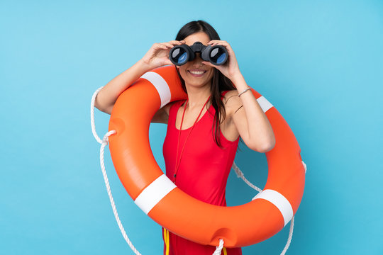 Lifeguard woman over isolated blue background with lifeguard equipment and with binoculars