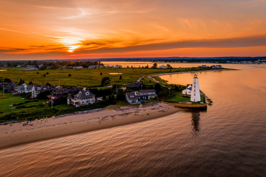 Summer sunset in Old Saybrook along the Connecticut River with Lynde Lighthouse in the foreground and a summer sunset