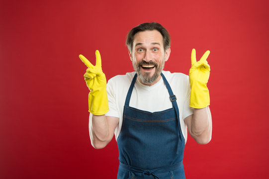 Happy relief every household day. Happy man show victory signs in rubber gloves. Household worker red background. Enjoying household routines. Cleaning and maintenance Providing household service