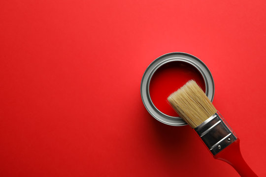 Paint can and brush on red background, top view