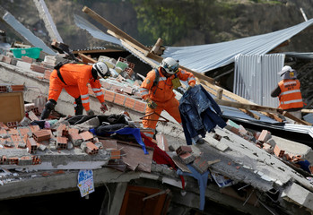 Members of a rescue team work on a collapsed building due to landslide following heavy rains in the Ovejuyo district in La Paz