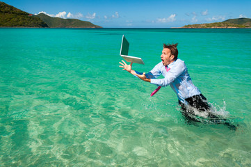 Shocked office worker leaping out of the water to catch his falling laptop computer in bright blue tropical sea