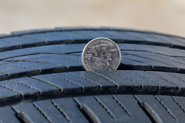 Closeup of checking tire tread wear depth of old tire using a quarter coin. Concept of automobile safety, maintenance, and repair Fotomurales