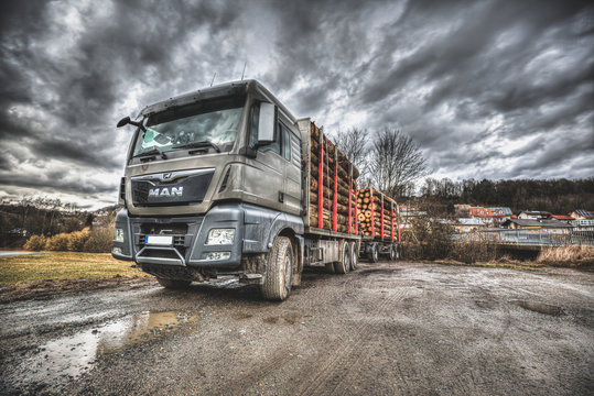 FREYUNG / GERMANY - FEBRUARY 23, 2020: MAN TGX 33.640 timber truck stands on a dirty road.