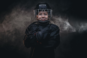 Young blonde fit boy, ice hockey player, posing in a dark studio for a photoshoot, wearing an ice-skating uniform with helmet, holding hands crossed while smiling on camera, close up portrait