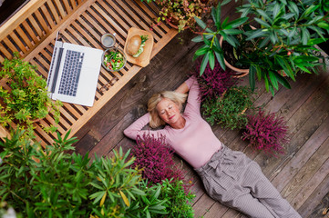 Poster de jardin Detente Top view of senior woman with laptop lying outdoors on terrace, resting.