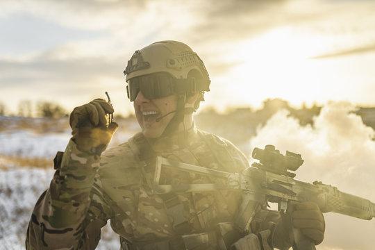 Modern war soldier army Man in multicam camouflage speaks on the walkie-talkie radio. equipment commandos with helmet and gun. soldier, sun backlight and smoke. modern warfare. atmosphere of skirmish