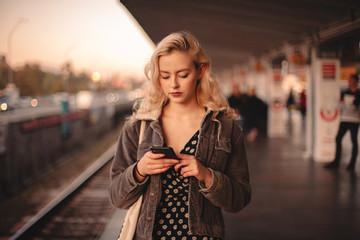 Young woman using smart phone waiting for train at subway station