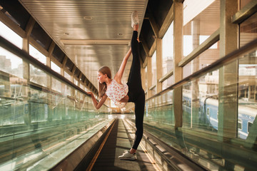 ballerina stands in a tunnel lifting her leg high