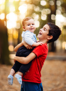 Portrait of adorable happy brothers, baby and preschool children, hugging outside in the autumn garden. Brother holds baby in his arms