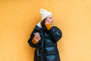 Young woman using smart phone while standing against yellow wall