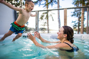 Young boy jumping into swimming pool, mom waiting to catch him.