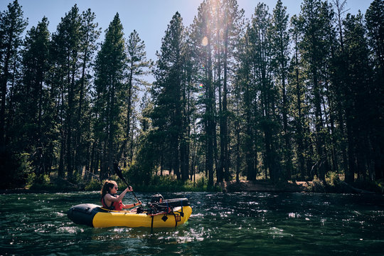Woman paddles her pack raft down the Deschutes River in central Oregon