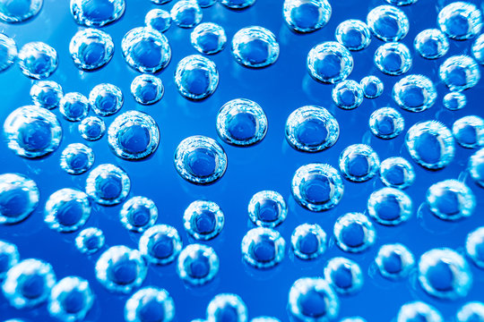 Bubbles of mineral water close-up. Macro photo in blue shades. Backgro