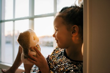 young girl looking lovingly at her toy at home at sunset