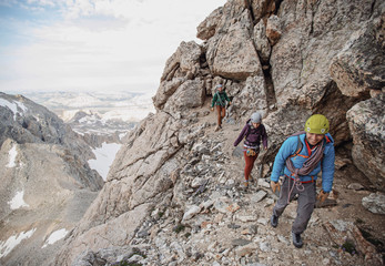 Three rock climbers hike along a cliff in the Tetons of Wyoming