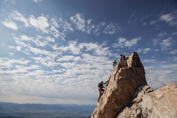 Three rock climbers each the summit of a mountain in Tetons, Wyoming
